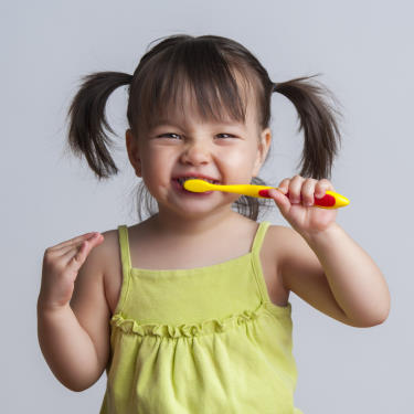 Little Girl with pig tails brushing her teeth